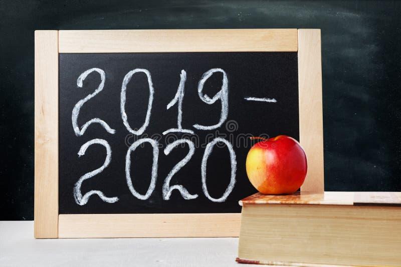 Zarząd szkoły z teksta akademickim rokiem 2019 2020 Tła czerni Szkolna deska, jabłko i książka, obrazy stock