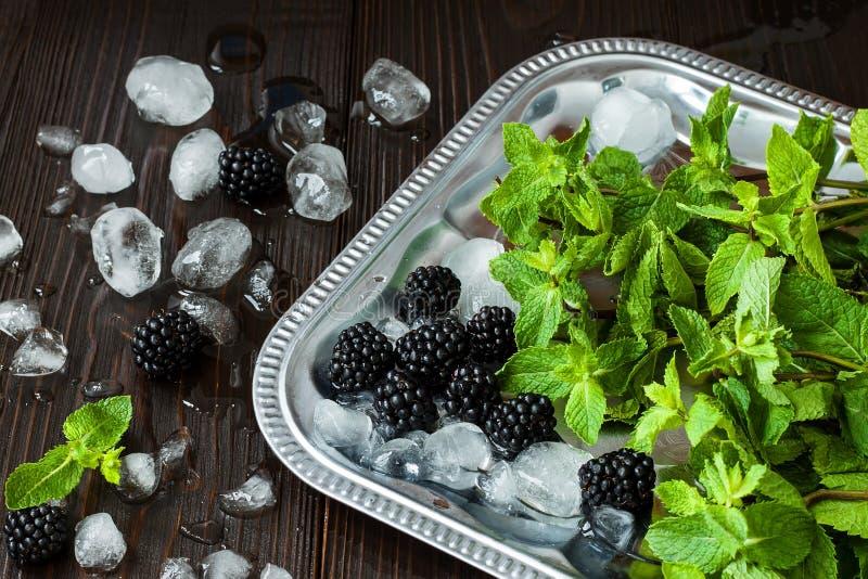 Zarzamoras y menta con hielo en la bandeja de plata sobre la tabla de madera rústica oscura Fondo del verano fotos de archivo libres de regalías