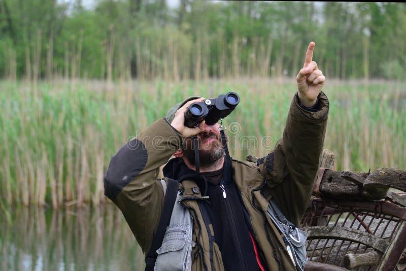 Zasavica, Σερβία - Απρίλιος, 19ο το 2014 : Άτομο με την προσοχή πουλιών διοπτρών που δείχνει το δάχτυλο επάνω στοκ φωτογραφίες