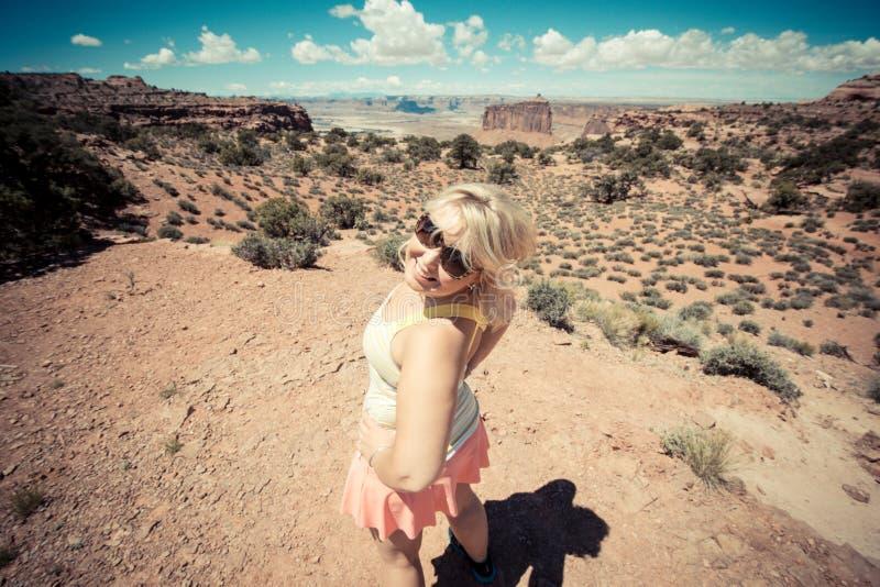 Zasięrzutny widok aktywna blondynki kobieta przewodził za podwyżce w Canyonlands parku narodowym w Utah dla Artystyczny filtr sto fotografia royalty free
