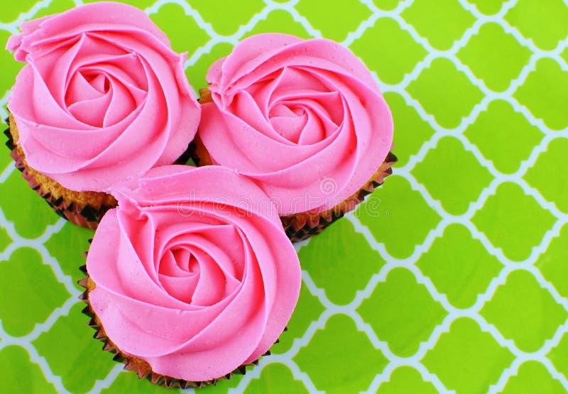 Zasięrzutny widok 3 babeczki z róża kształtującym różowym mrożeniem zdjęcie stock