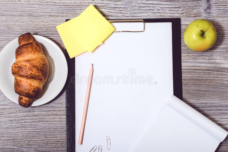 Zasięrzutny widok biuro accessorise: schowek, smakowity, croissant fotografia stock