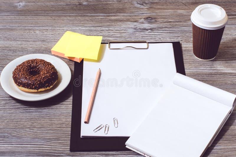 Zasięrzutny widok biuro accessorise: schowek, smakowity pączek, papka zdjęcia stock