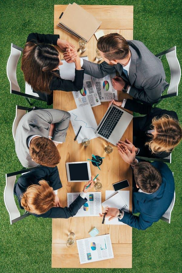 zasięrzutny widok dwa partnera biznesowego robi ręki zapaśnictwu podczas gdy koledzy pracuje przy stołem zdjęcia stock