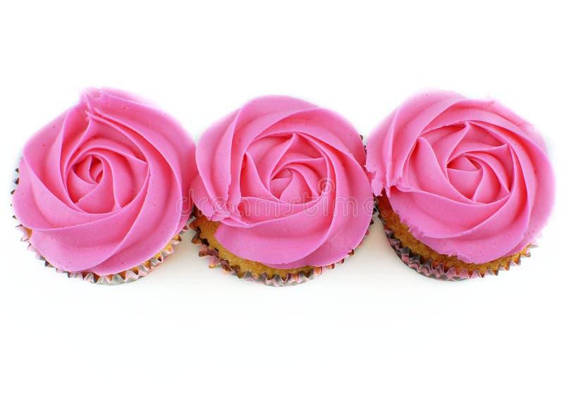 Zasięrzutny widok trzy babeczki z menchiami, róża kształtował mrożenie na białym tle fotografia stock