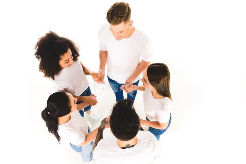 zasięrzutny widok wieloetniczna grupa młodzi ludzie trzyma ręki i pozycję w okręgu odizolowywającym fotografia stock