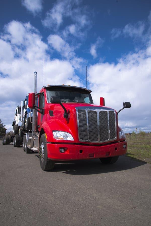 Zasila dużą takielunek czerwieni ciężarówkę odtransportowywa inny semi semi przewozi samochodem dalej obrazy royalty free