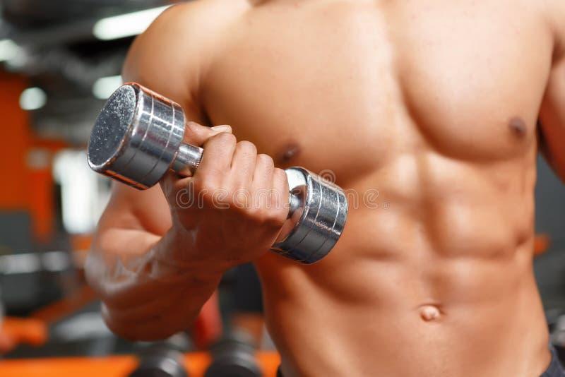 Zasila lifter pracującego z dumbbells w gym out obraz stock