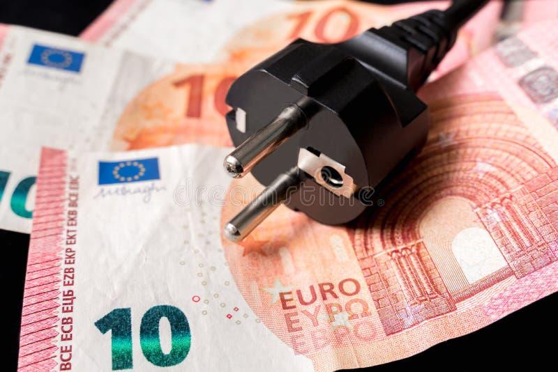 Zasilanie elektryczne prymka i europejczyka pieniądze na tle fotografia stock