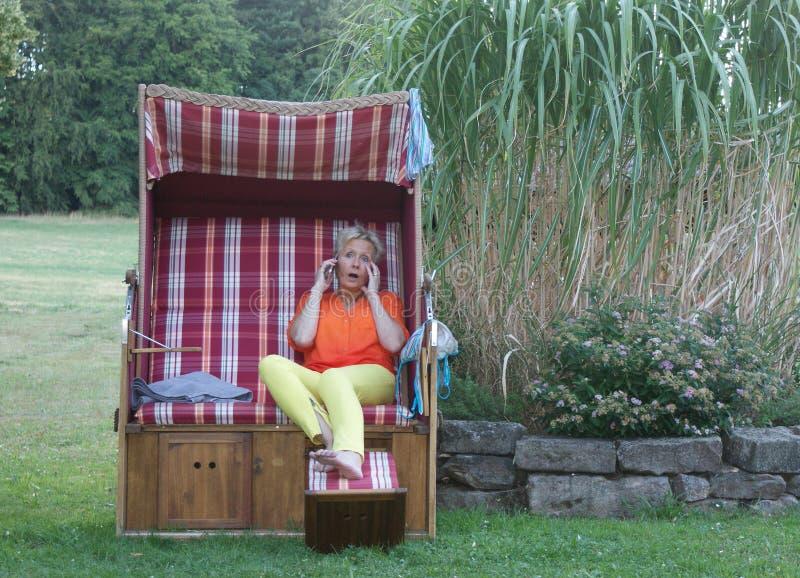Zaskakująca wiadomość dosięga młodej kobiety w zadaszającym łozinowym plażowym krześle z jej smartphone fotografia royalty free