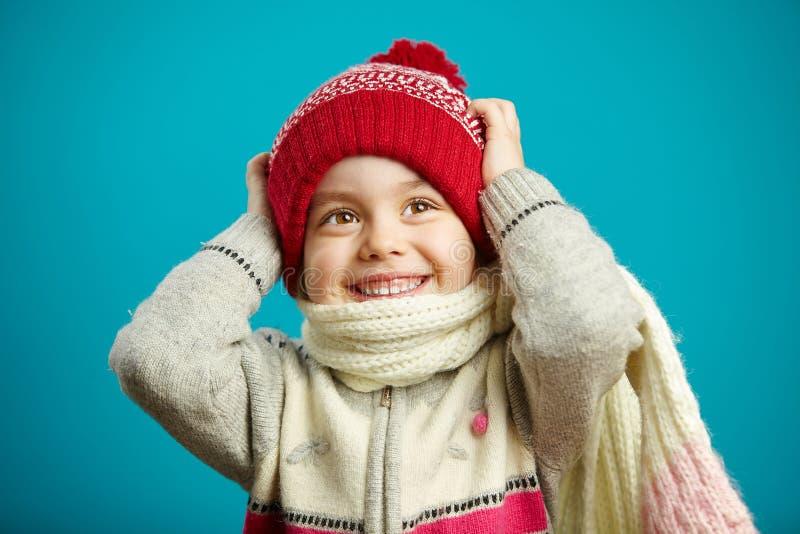 Zaskoczona dziewczynka w świątecznym kapeluszu, która chwyciła głowę, wyraża zdziwienie i zdumienie, stoi na niebieskim tle fotografia royalty free