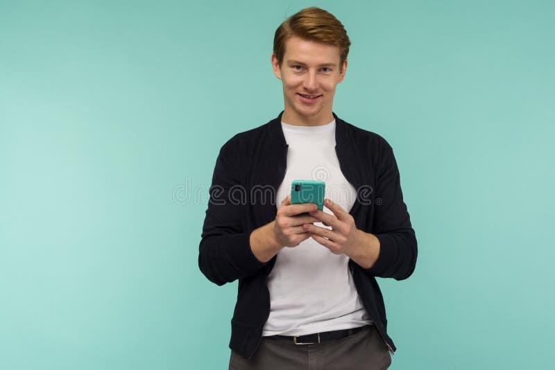 Zaskoczony sportowy czerwonowłosy facet dostał wiadomość na smartfonie na niebieskim tle obrazy stock