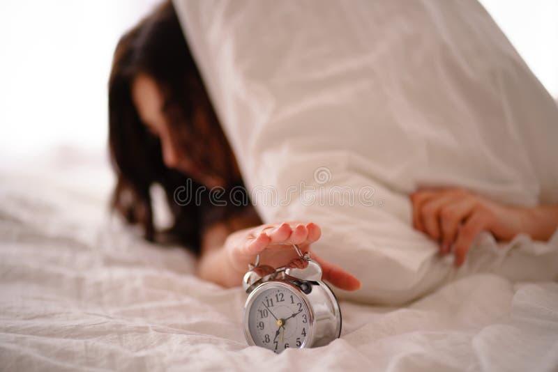 Zaspanie kobieta budzi się obracający daleko budzika obrazy stock