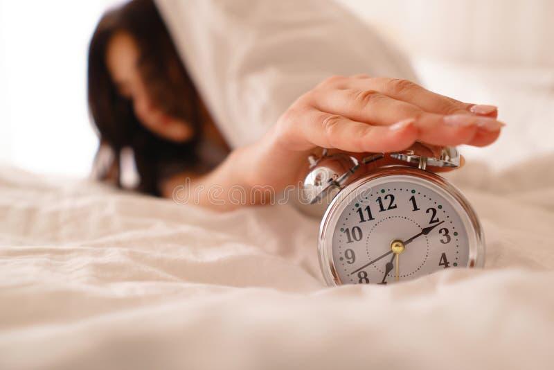 Zaspanie kobieta budzi się obracający daleko budzika fotografia royalty free