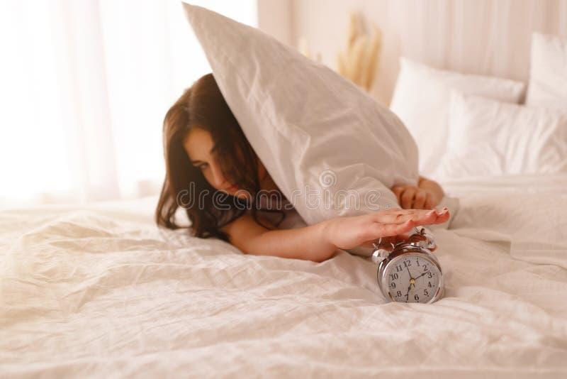 Zaspanie kobieta budzi si? obracaj?cy daleko budzika fotografia stock