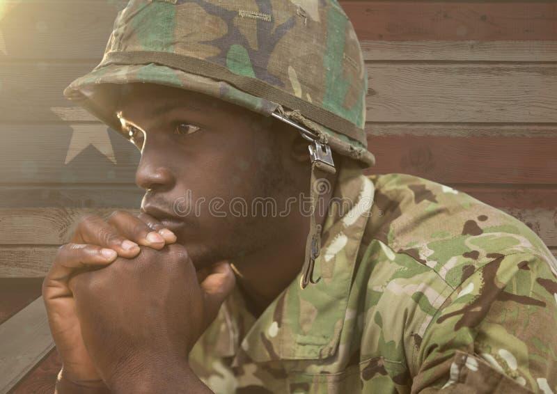 Zastanawiać się żołnierza przeciw drewnianemu flaga amerykańskiej tłu zdjęcia stock