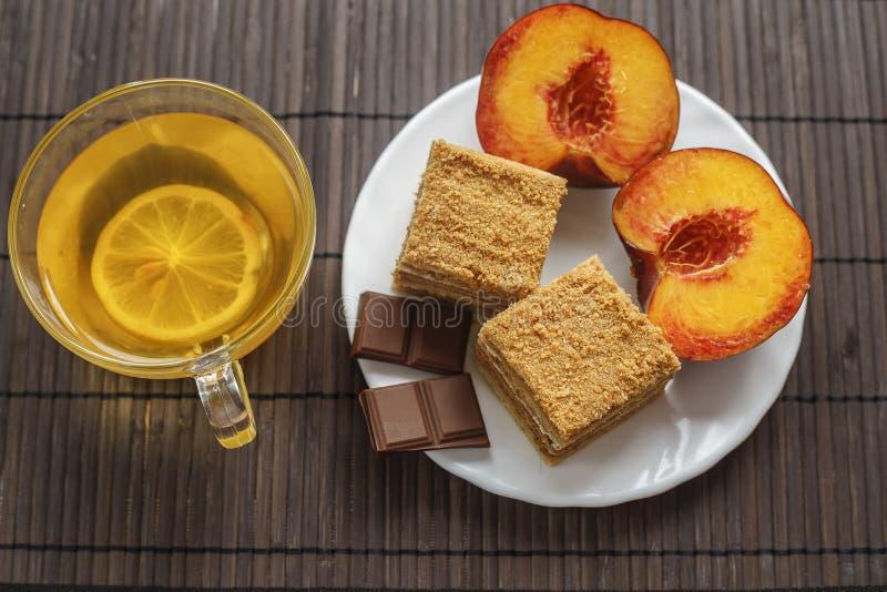 Zasycha z filiżanką herbata na ciemnym drewnianym tle Deser chałupa ser w czekoladowym glazerunku obrazy stock