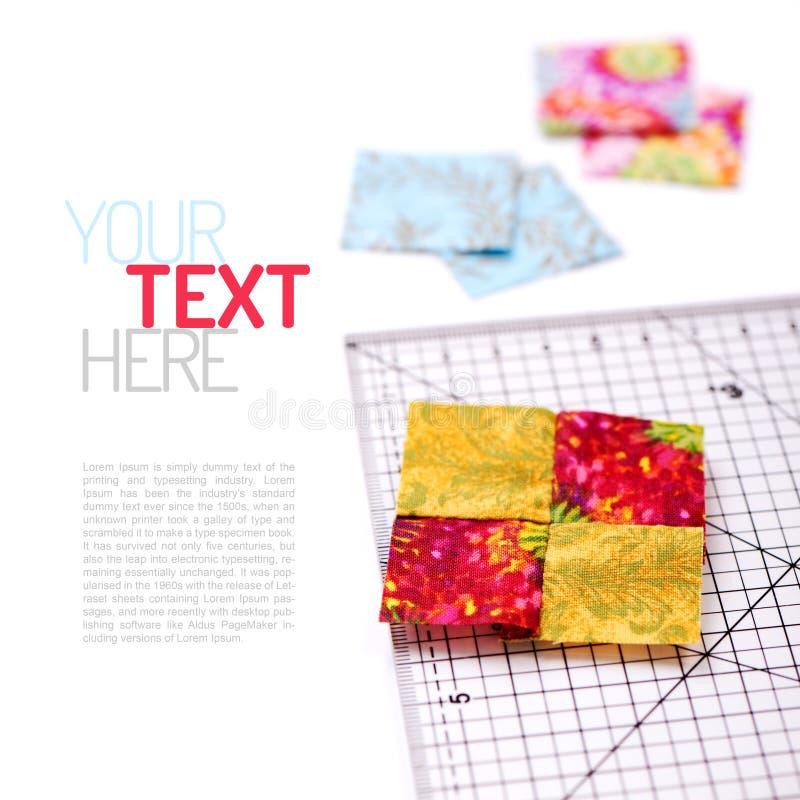 Zaszyci kwadratowi kawałki tkanina kołderka i władca na białym sura fotografia stock