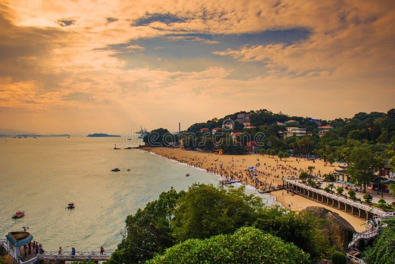 Zatłoczona plaża pod złotymi chmurami obrazy royalty free