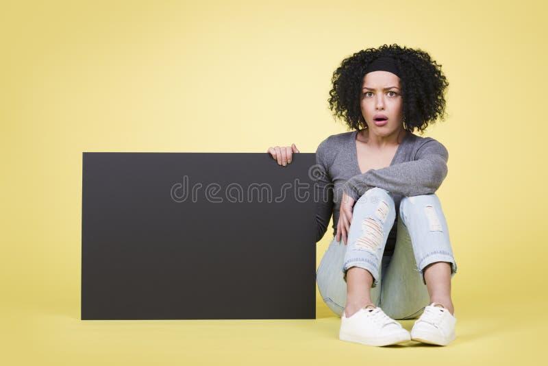 Zataczająca się dziewczyna trzyma czarną puste miejsce znaka deskę z copyspace fotografia stock