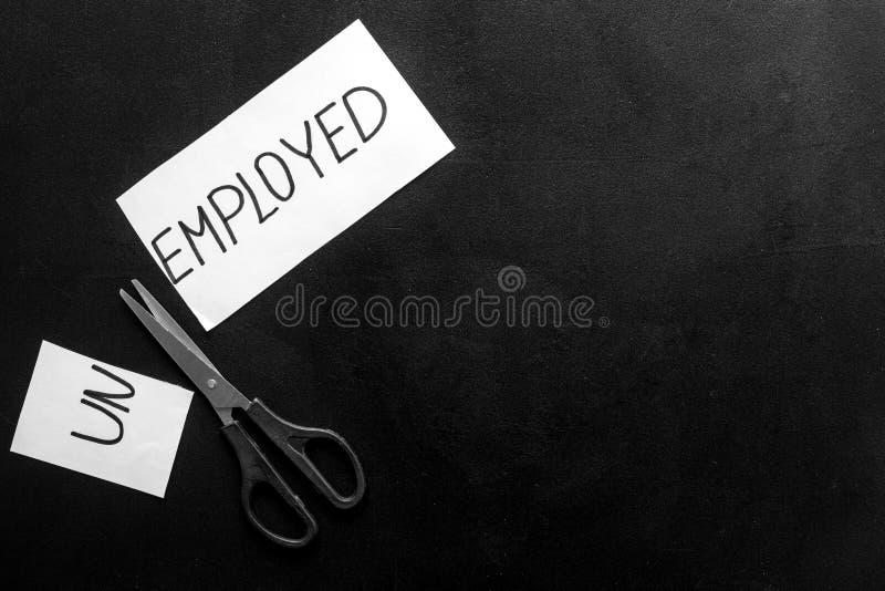 Zatrudnienie, nowa koncepcja zatrudnienia Arkusz papieru rozdartego — bezrobotny — nożyce na czarnym stole z góry na dół obraz stock