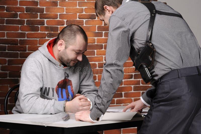 zatrzymany przesłuchuje oficer policję zdjęcie royalty free