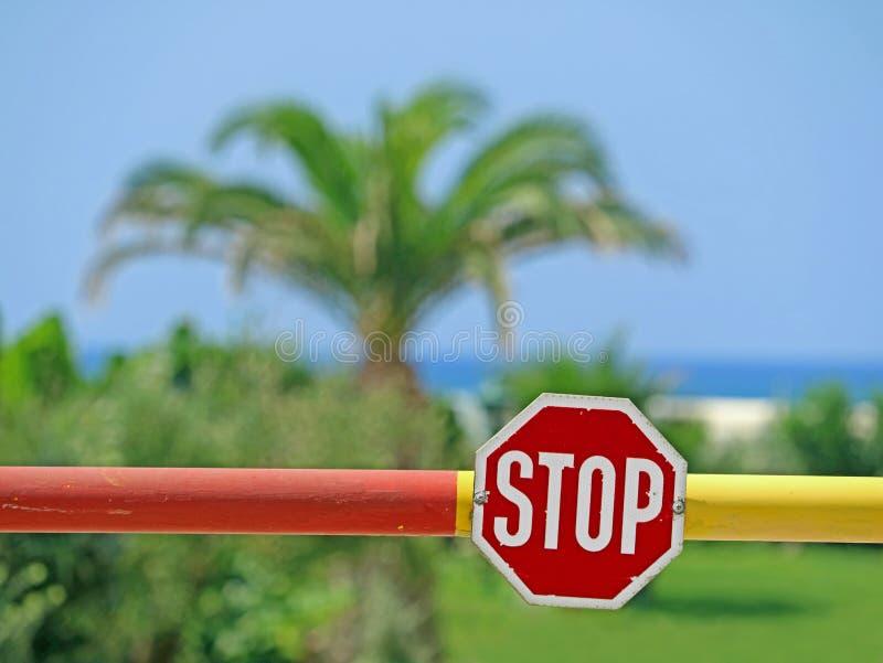 Zatrzymuje znaka na barierze z drzewkiem palmowym, niebieskim niebem i morzem w tle, pojęcie podróży kasowanie obrazy stock