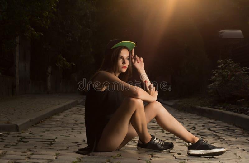 Zauber Brunettemädchen im Sportkleid, das auf den Kopfsteinen an sitzt stockfotos