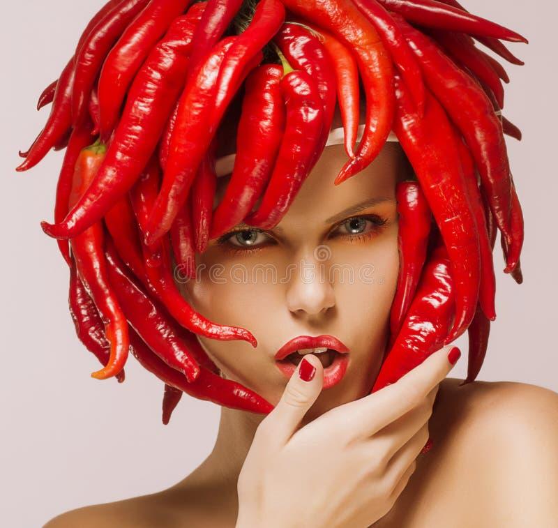 Zauber. Heißer Chili Pepper auf dem Gesicht der glänzenden Frau. Kreatives Konzept lizenzfreie stockfotografie