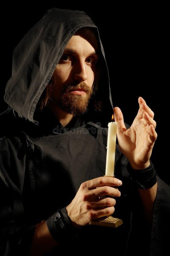 Zauberer mit brennender Kerze stockfoto