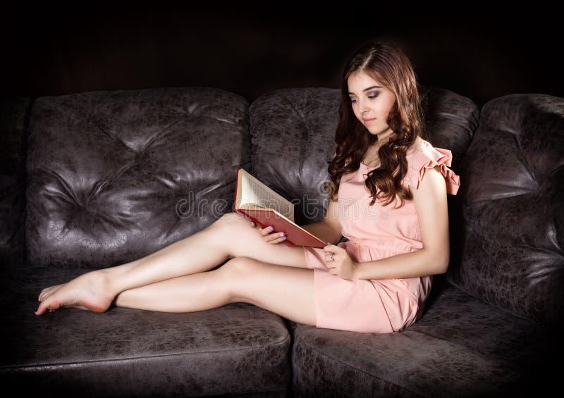 Zauberfrau in einem rosa Kleid, das auf einem ledernen Sofa sitzt, las ein Buch stockbild