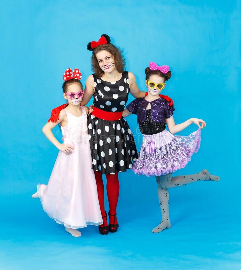 Zauberfrau und zwei Mädchen in den Parteikostümen auf blauem Hintergrund stockfoto