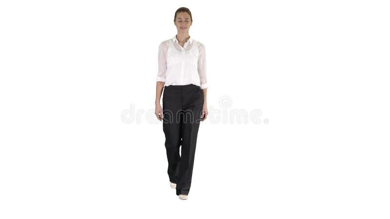 ZauberGeschäftsfrau, die mit den Händen in ihren Taschen auf weißem Hintergrund geht stockfoto