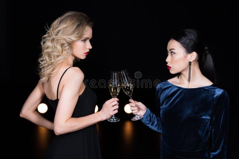 Zaubermädchen in den Abendkleidern, die mit Champagnergläsern an der Partei klirren stockfotos