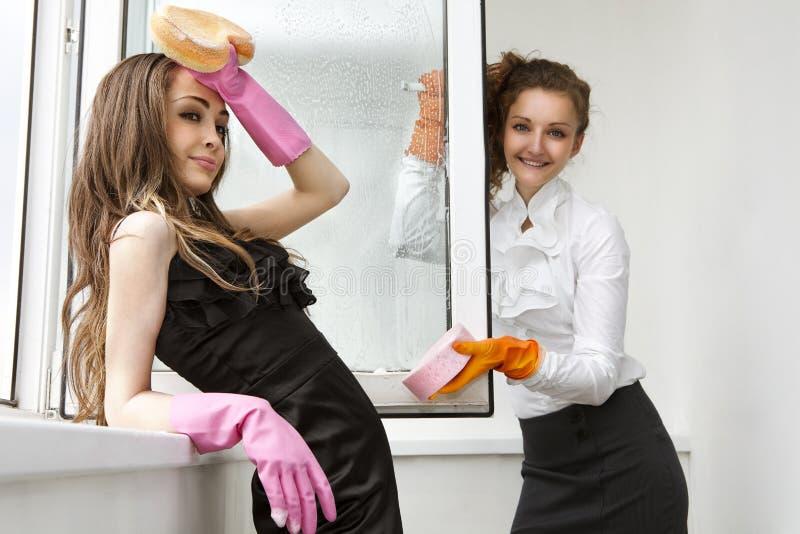 Zaubermädchen, die das Fenster waschen stockfotografie
