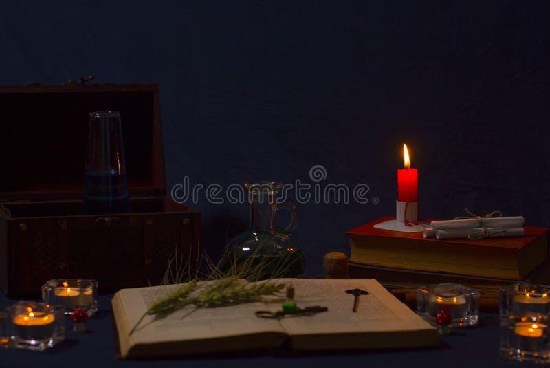 Zaubertrank, alte Bücher und Kerzen auf dunklem Hintergrund lizenzfreie stockfotografie