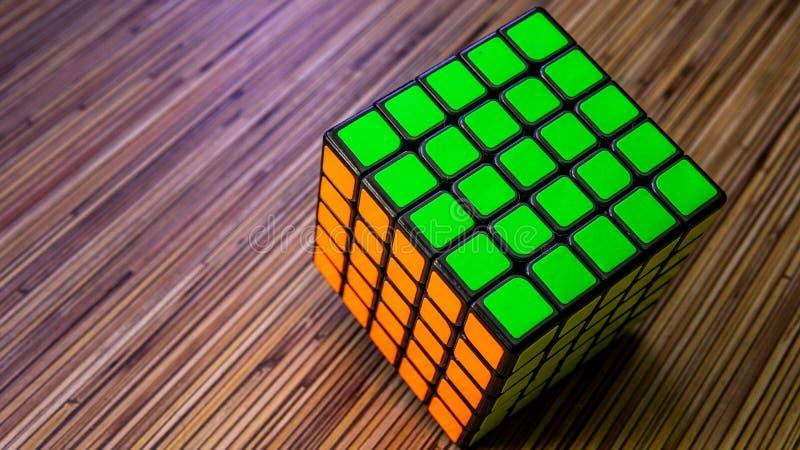Zauberwürfel 5x5 auf einem Holztischhintergrund stockfotografie