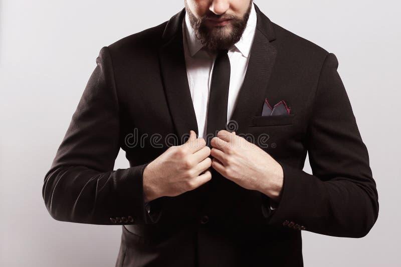 Zaufanie i charyzma Przystojny młody człowiek przystosowywa jego kurtkę w pełnym kostiumu zdjęcie royalty free