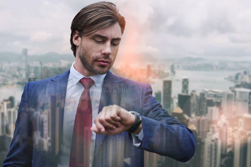 Zaufanie i punktualność Ruchliwie młody biznesmen patrzeje jego zegarek w kostiumu podczas gdy stojący przeciw nowożytnemu obraz royalty free