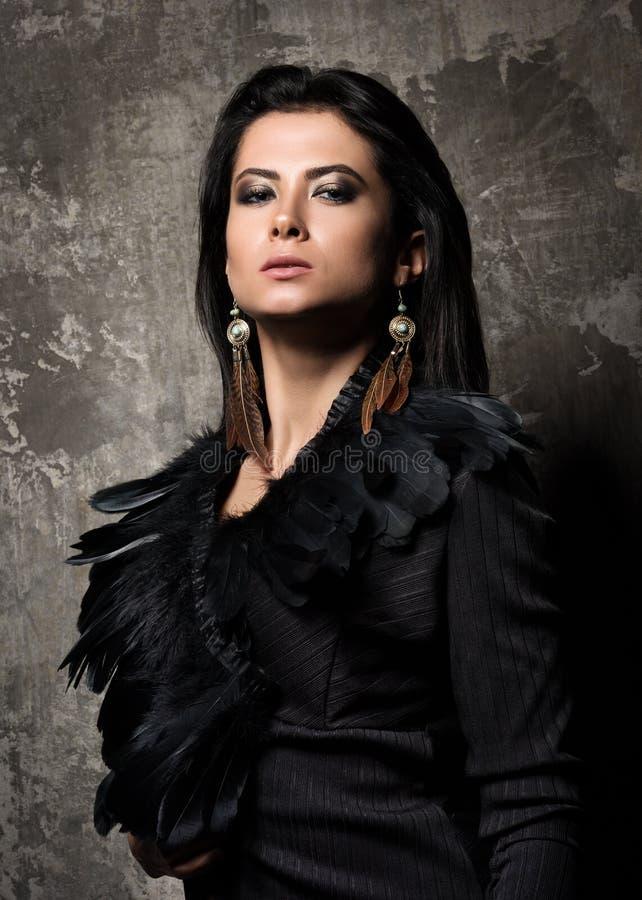 Zaufanie i władza Portret młoda piękna kobieta z ciemnym włosy Suknia i kolczyk z piórkami fotografia royalty free
