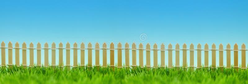 Zaun als Grenze vom Garten auf Wiese als Titel stockbilder
