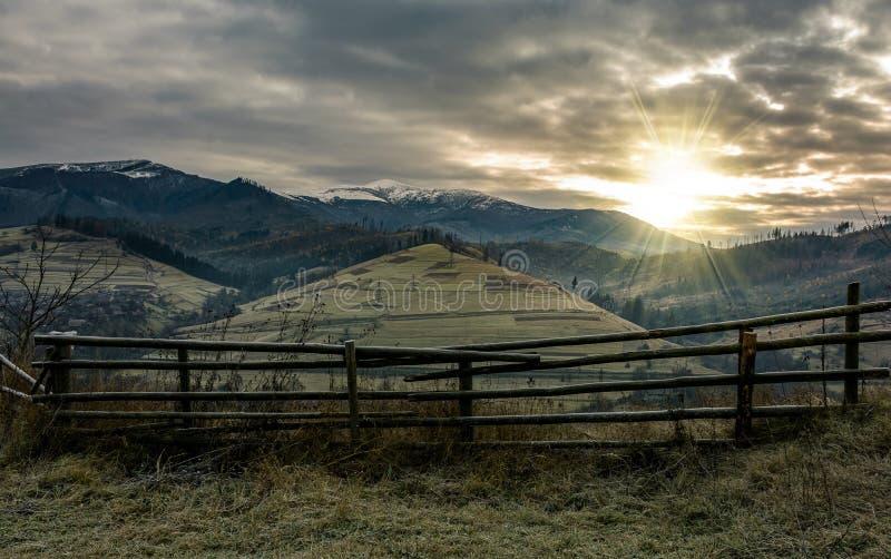 Zaun auf Abhang im düsteren Sonnenaufgang des Spätherbsts lizenzfreies stockfoto