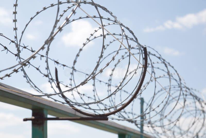 Zaun mit Rasiermesserstacheldrahtschutz gegen Hintergrund des blauen Himmels Diktatur- und Tyranneikonzept lizenzfreies stockbild