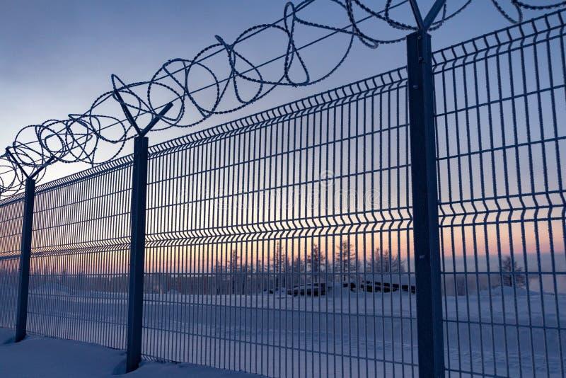 Zaun mit Stacheldraht auf der Grenze des Gegenstandes an der Dämmerung im Winter Norilsk stockfoto