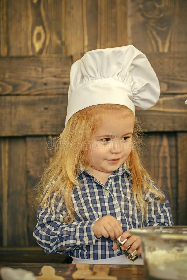 Zawód kucharz Chłopiec piekarz w szefa kuchni kapeluszu z ciastko krajaczem fotografia stock