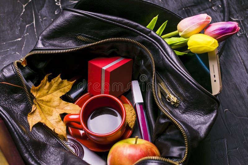 Zawartość żeńska torebka Kwiaty, pomadka, kamera, kawa, ciastka, koraliki Być może obrazy royalty free