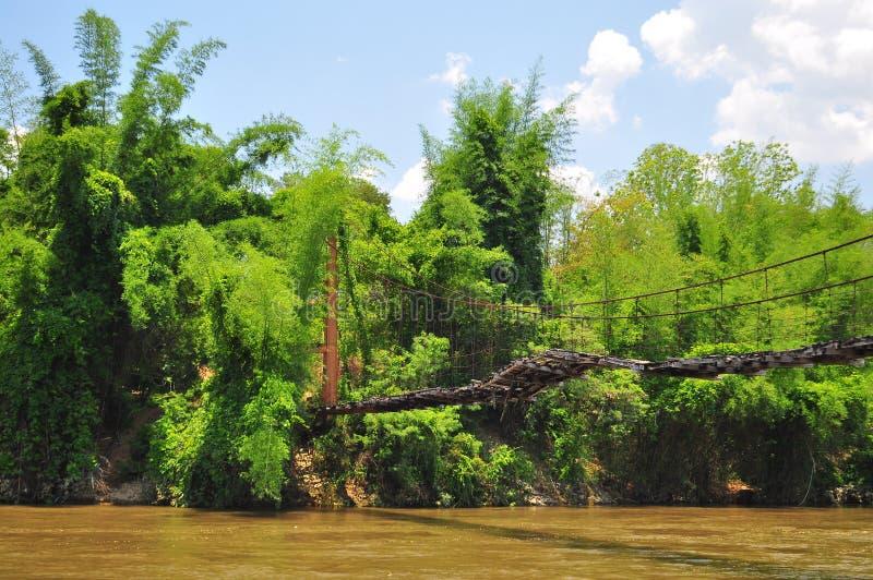 Zawieszony drewniany most nad rzeką prowadzi dżungla w Tajlandia fotografia stock
