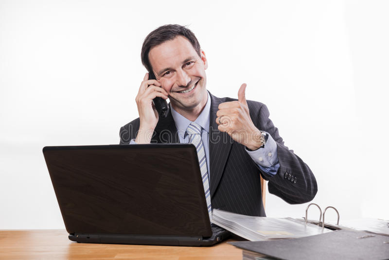 Zawiniony pracownik ono uśmiecha się przy telefon aprobatami fotografia royalty free