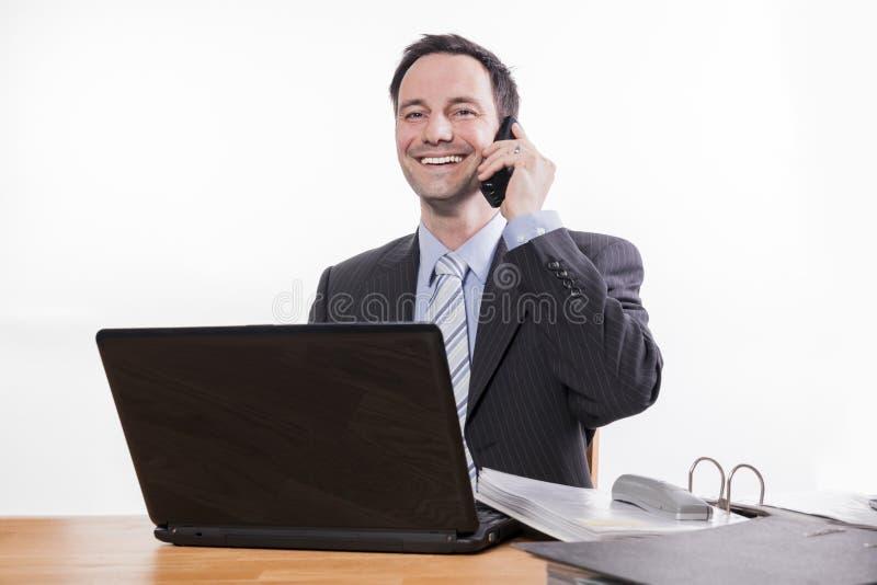 Zawiniony pracownik ono uśmiecha się przy telefonem fotografia stock