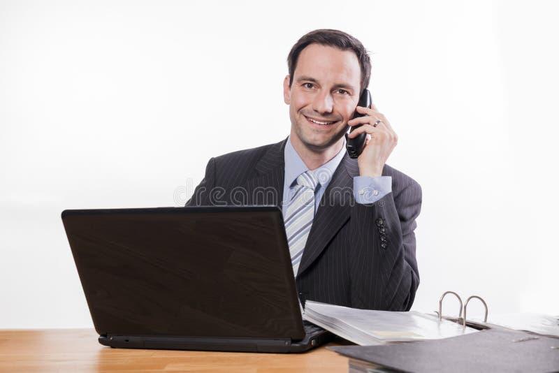 Zawiniony pracownik ono uśmiecha się przy telefonem zdjęcie royalty free